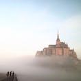 ▶︎フランス🇫🇷モン・サン・ミシェル  こちらは、モン・サン・ミシェル内のホテルに泊まった翌日の朝少し早起きをして撮りに行った写真です。以前あげた紫がかった空も同日に撮った写真ですが、霧ががって幻想な雰囲気のあるこちらもお気に入りです✨ ご覧の通り一緒に行った友人達は見えますが、橋の終わりはもう霧で見えません😄  パリから日帰りツアーもありますが、是非少し長めに訪れて時間による景色の移ろいを感じてみて下さい🦋
