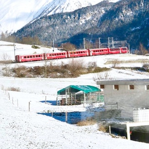 Cadera Station カデラ駅 Bernina Express ベルニナ急行 Ratische Bahn レーティッシュバーン鉄道 Switzerland スイス World Heritage Site 世界遺産 下り列車との待ち合わせで、雪山へと消えていった真っ赤な車体