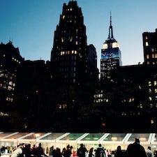 New York / Manhattan Bryant Park ブライアントパークから見える青く光り輝くエンパイアステートビル。