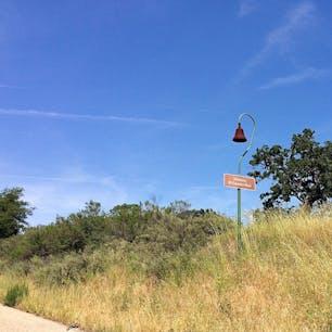 王の道(カリフォルニア)  西海岸のEl Camino Real(王の道)と呼ばれる道路を走っていると、沿道に点々と現れるミッション・ベル・マーカー。  植民地計画の下、スペインから上陸したフランシスコ会修道士フニペロ・セラ神父が、1769年から1823年にかけて、サンフランシスコ・サンディエゴ間の約965kmに、21のミッション(伝道所)とその補助的施設を建設。  開拓を通して踏み固められていった路地は王の道と呼ばれ、やがて車道となり、いろいろな物を生み出していく原点に。  1900年代初め、かつて伝道所での生活において欠かせなかった鋳物の鐘を模した道標が、王の道沿いに1マイル間隔で設置され、道路交通の重要な発展へと繋がる。  カリフォルニア州歴史史跡の一つで、植民地時代の名残を垣間見るアイコニックな表象。  #missionbell #missionbellmarker #california #elcaminoreal #historiclandmark