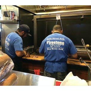 サンルイス・オビスポ(カリフォルニア)  厨房から立ち上る煙と、十字路に面した広いテラス席が目印の、ファイヤーストーン・グリル(Firestone Grill)。  ダウンタウンで、手軽にしっかりお肉が食べられるお店。屋外もストーブ完備。  その土地によって独自のバーベキューがあるように、セントラル・コーストでは、サンタマリア・スタイル・バーベキューと呼ばれるものが一般的。  元々、サンタマリア渓谷に伝わる伝統的な料理で、トライ・ティップ(ボトム・サーロインの中の部位で、重さ約1キロ、長さ40センチほどの二等辺三角形をしている)を、塩と胡椒、ガーリックソルトなどで味付けをして、オーク材でグリルしたもの。レシピやメニューの著作権は、サンタマリア渓谷の商工会議所が保有しているそう。  お肉やパンを焼くのも、ハンドルを回すと厚い鉄板が上下する大きなグリル網を使うのが特徴。この辺りは風がよく通り抜けるので、屋外で火があおられて大きくなっても、遠火に調節できるのが利点。  ちなみにこのスタイルのグリル器械は、郡立公園などのレクリエーション・エリアにも同等のサイズのものが置かれていて、予約制で自由に使えるようになっていたりする。  #sanluisobispo #california #bbq #tritip #firestonegrill