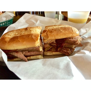 サンルイス・オビスポ(カリフォルニア)  お店オリジナルのBBQソースがほどよく絡んだトライ・ティップ・ステーキを、ガーリック・ブレッドで挟んだ、シンプルなサンドウィッチ(tri-tip steak sandwich)。ファイヤーストーン・グリル(Firestone Grill)にて。  ほとんど脂のない赤身で、柔らかい厚切りお肉のミルフィーユは、同じ高さに口が開かないほどのボリューム。しっかりお腹を満たしてくれるフォトジェ肉なメニューが揃っていて、リピーターが多いのも納得。  そんな、お肉と炭火のマリアージュの虜になっている人が五万といるアメリカのBBQ事情。  とある不動産関連会社が弾き出した統計によると、アメリカで最もBBQを愛しているのはアラバマ州だそう。ちなみに1位〜15位まで南部の州が占めている。  その愛を測るものさしはいろいろあるだろう中、この会社独自の基準は、州毎の、1)住民1人当たりに対するBBQレストランの数、2)Facebook上での情報数、3)BBQのカテゴリーに分類されているレストランの数、4)Googleサーチでbarbecueと検索された数、5)BBQ用品や炭の生産者の数、の各項目を調査した結果だそう。  アメリカが広いからこそ、コミュニティ単位でまとまると、その温度差はさらに大きく広がる。本格的にBBQを食べる地域か否かは、その土地で暮らした場合に、日々のご近所付き合いや地元のパーティーなどで集う際の楽しみ方にも大きな違いが。  BBQ愛好家がお家探しをするときに、間違ったエリアを選んでアウェイな辛い思いをしないようにとの配慮から、同社があくまでもお客様のための参考資料用に行った、真面目なリサーチなんだとか。どこまでも深い、アメリカのBBQ愛を感じる。  #sanluisobispo #california #bbq #tritipsandwich #firestonegrill