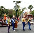 アナハイム(カリフォルニア)  ディズニー・カリフォルニア・アドベンチャー・パーク(Disney California Adventure Park)の、ブエナ・ビスタ・ストリート(Buena Vista Street)にて。  1920年代のロサンゼルスを再現した街並みで、パークの玄関口に当たる。  ボーカリストの女性ダイムと、シカゴから到着したばかりのクインテット(Five & Dime)が歌って踊る、20分ほどの素敵なショー。  アイ・ガット・リズム(I Got Rhythm)などに代表される、1920〜1930年代のジャズが数珠つなぎに演奏される。軽快なテンポに、周囲のお客さんたちも惹き込まれてスウィング。  ボーカリストの女性の後ろに僅かに見える像が、パークのアイコンになっているフォト・スポット、ストーリーテラー像(Storytellers Statue)。  1923年にカンザス・シティからロサンゼルスに来た当時の、若かりし頃のウォルト・ディズニーとミッキーの姿。  #buenavistastreet #californiaadventure #anaheim #waltdisney #fiveanddime