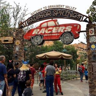 アナハイム(カリフォルニア)  ラジエーター・スプリングス・レーサー(Radiator Springs Racers)のエントランス。  ディズニー・カリフォルニア・アドベンチャー・パーク(Disney California Adventure Park)にて。  映画「カーズ」シリーズとルート66にインスピレーションを受けて作られたカーズランド。他2つのアトラクションや、フローのV8カフェ(Flo's V8 Cafe)などのレストランやお店が、ラジエーター・スプリングスを再現した世界に広がっている。メイン・ストリートはルート66がモチーフ。  6人乗りのレース・カーに身を沈めたら、カラフルな岩肌やキャデラック・レンジの南西部風景、流れ落ちる滝を見ながら、オーナメント・バレーを軽くドライブ。  カーマニアなら、6つの山々の頂が、1957年〜1962年モデルのクラッシックなキャデラックの、テール部分に似ていることに気づくのでは。  この山並は、ルート66沿いのテキサス州アマリーリョの街にある、キャデラック・ランチのパブリック・アート(ペイントされたキャデラックが10台、地面に突き刺さった状態で並んでいる)が元になっているそう。  やがてラジエーター・スプリングスの夜の街に到着すると、レースに向けてマックィーンやサリー、メーターなど全員がお出迎えしてくれ、カーズの世界が目の前に。  いよいよ車のチューンナップのため、ルイージのタイヤのお店、もしくはラモーンのボディペイントのお店へ。どちらに行くかは自分では決められないので、その時次第。  調整を済ませてお店を抜けると、対戦相手と横並びに。一呼吸おいて、スタート。2台が常に競り合いながら、後は一気にフィニッシュ・ラインまで高速で駆け抜ける。  アップダウンがあったり、軽いコーナリングで体が傾いたり、ふわっとお腹がすくような感覚は受けるけれど、走りもとてもスムーズで、ジェットコースター系が苦手でも乗れる程度のほどよいスリルが味わえる。  午前と午後で1回ずつ搭乗し、もうあと2〜3回乗りたかったと思うほど楽しかった、ここだけのアトラクション。昼と夜では雰囲気や迫力も違うので、時間帯を変えて乗るのもお勧め。  #carsland #california #adventurepark #anaheim