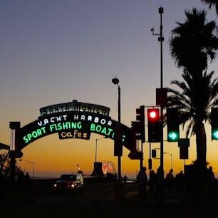 サンタモニカ(カリフォルニア)  サンタモニカ・ピア(Santa Monica Pier)のゲート。  ブックストアや雑貨店、カフェを巡ったり、街歩きも楽しいサンタモニカ。ダウンタウンを抜けて海辺に向かう、コロラド・アベニューにて。  遠くに小さく、パシフィック・パークのライトアップされた観覧車(Solar Ferris Wheel)が映る。  太陽光発電で動くこの観覧車は、シーズンやイベントごとに装いを変え遠くからもよく目に入るけれど、唯一アース・アワー(Earth Hour)には1時間灯りが消えるそう。  毎年3月最終土曜日の夜8時半〜9時半にかけて行う、地球環境を守りたいと言う意思表示の消灯運動。日本からは、東京タワーや東京スカイツリー、みなとみらいのコスモ・クロック21他。  2007年にシドニーから始まったムーブメントで、年々規模が拡大。南太平洋のサモアから始まりクック諸島で消灯リレーが終わった2020年は、過去最高の190ヶ国7,000都市以上が参加。  同時刻に家の大きな灯りを消して賛同した家庭も少なくなかったようで、光が戻った時に改めてそのありがたみを感じる。  #santamonicapier #california #earthhour #sunset #地球とつながろう