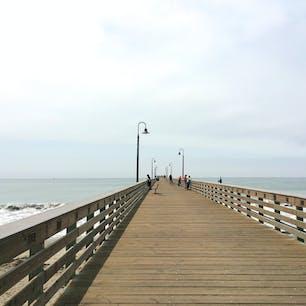 カユーコス(カリフォルニア)  L.A.とサンフランシスコの中間くらいに位置する、セントラル・コーストの海沿いの小さな街、カユーコス(Cayucos)。  エステロ湾(Estero Bay)に架かるカユーコス・ピア(Cayucos Pier)にて。  かつては先住民のチューマッシュ族が住んでいた。1867年に東海岸からやって来た船乗りが、この地がチーズや牛肉、なめし革などの貿易の拠点に向いていると判断し移住したのが街の始まり。  カユーコスと言う名は、スペイン語のカヌーやダグアウト・ボートの意味から付けられたそう。  夏は涼しく冬も温暖な気候に恵まれ、一年を通してバカンスに訪れる人が絶えないエリアのひとつ。  桟橋からの釣りも一般開放されていて、湾内ではスキンダイビングやサーフィン、カヤックなども楽しめる。  #cayucos #california #pier