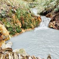 登別温泉:地獄谷の裏側あたりの山奥にある、20㌢位のほんのり暖かい硫黄泉の足湯。地獄谷の源泉から流れ来ているとの事。白人系の外人さんが先客で楽しんでいて、穴場なのに良く知っているなって驚きました。