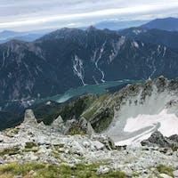 2021.9.12 立山山頂3015mから黒部ダムを見下ろす 小さくてわかりにくいけれど 左中央→黒部ダムのアーチ 右上→うっすらと富士山 右側→氷河? 黒部湖を走る遊覧船も見えるね